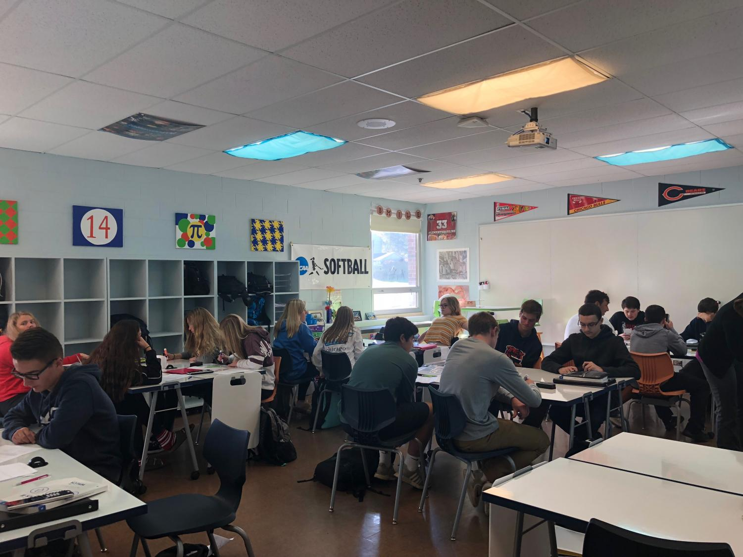 Students in Mrs. Johnson's math class are utilizing the whiteboard desks to practice problems. The whiteboard desks are currently aiding them to learn how to graph quadratic functions using a table of values and an axis of symmetry.