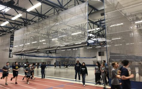 PE students running laps in the fieldhouse and begin to stretch in preparation for a day of challenging fitness ahead.