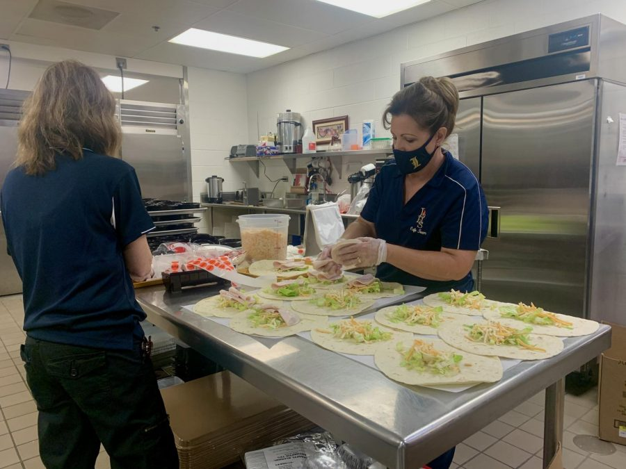 Cafeteria staff members Lori Thompson and Denise Barbour preparing turkey wraps entrees. The wraps included turkey, lettuce, and shredded cheese. That day students got the turkey wrap along with a bag of chips, fruits and vegetables varying from student to student, bagels studded with cream cheese, and juice.