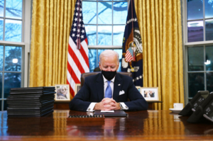 President Joe Biden sits in the Oval Office, his new home for the next four years.
