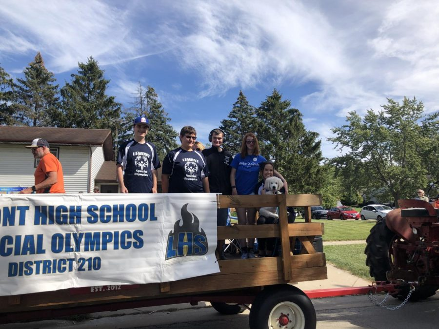 Maddie, Cooper, and the Special Olympics Team wave to bystanders from their parade float provided by the Tractor Club.