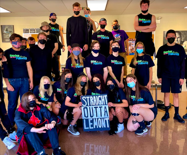 A senior class poses with a class poster while waiting for the class color day games assembly.